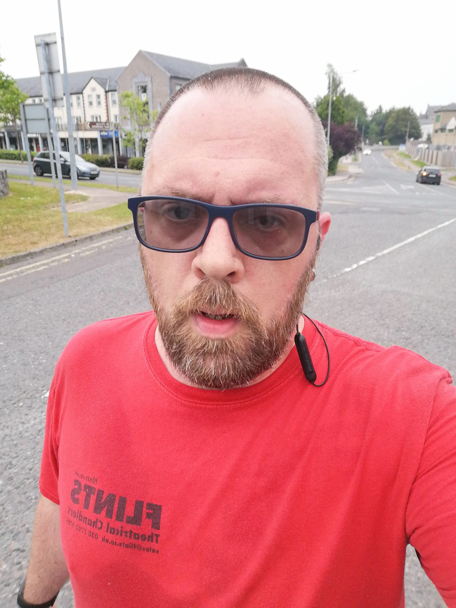 A man in a red t-shirt with sunglasses running on a tarmac road