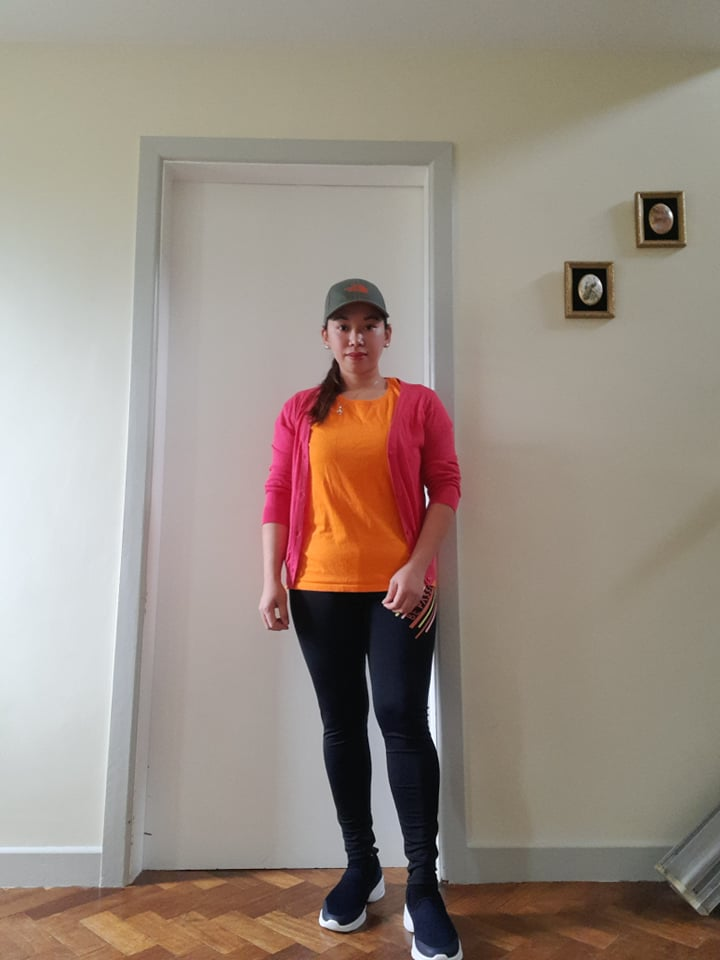 A woman in an orange t-shirt in front of a white door