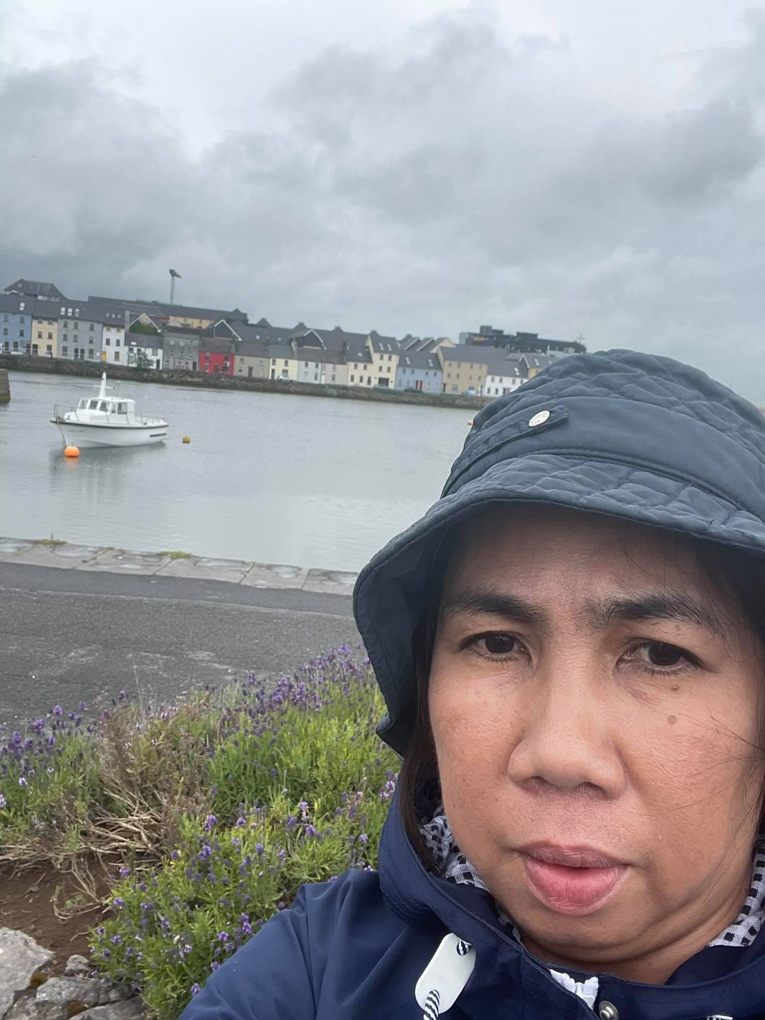 A woman in front of a harbour in a raincoat