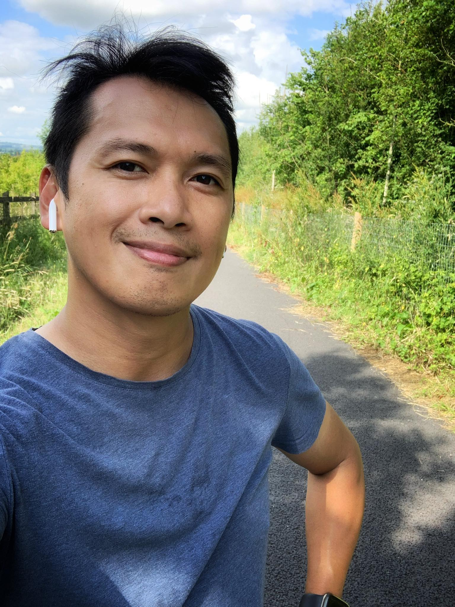 A man smiling on a country road during his run