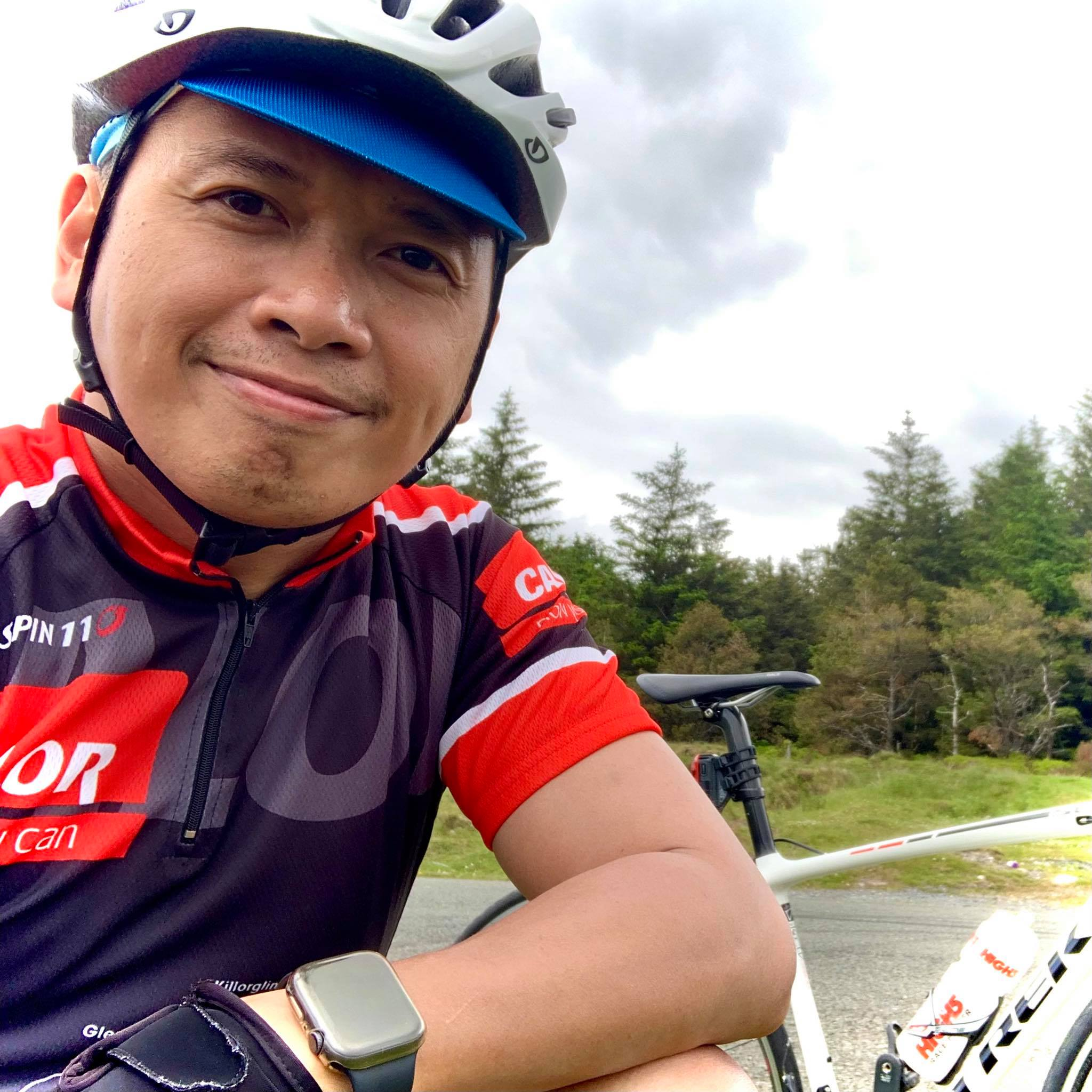 A man smiling with a cycling jersey and helmet in front of his bike near a forest