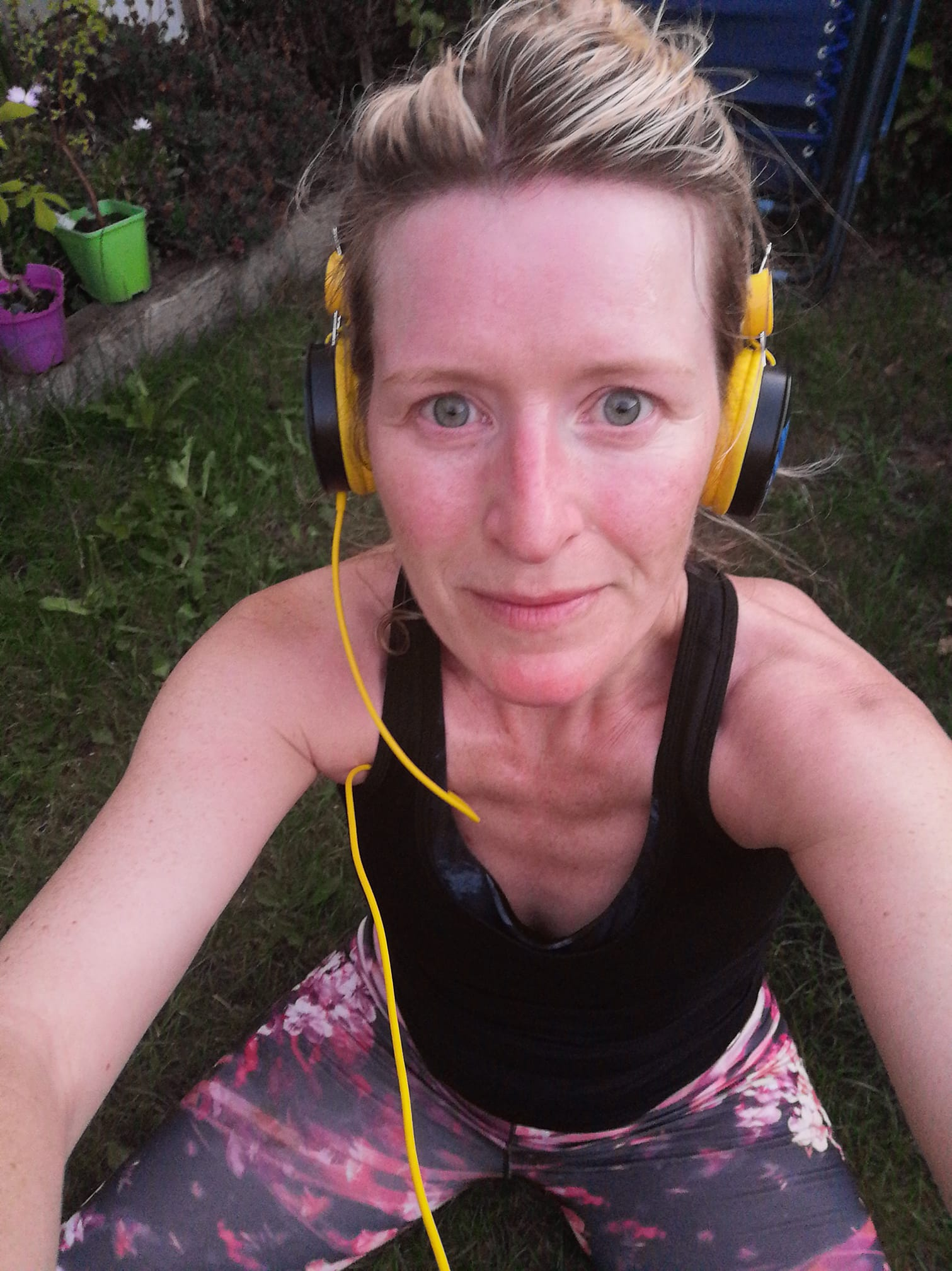 A woman taking a selfie post-fundraising run with yellow headphones.