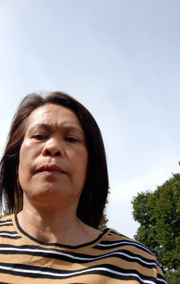 A woman in a yellow and black striped t-shirt with a blue sky in the background.