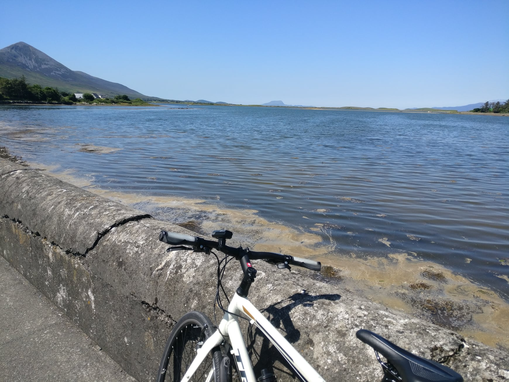 A white bike leaning against a stone wall in front of a lake in Mayo