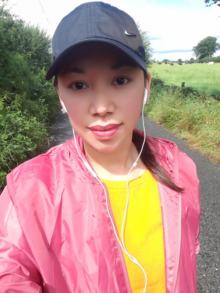 A woman with a pink jacket, yellow t-shirt, white headphones and a navy cap with a country road in the background.