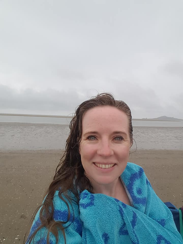 A woman in a blue towel standing in front of a cloudy sky and sandy beach.