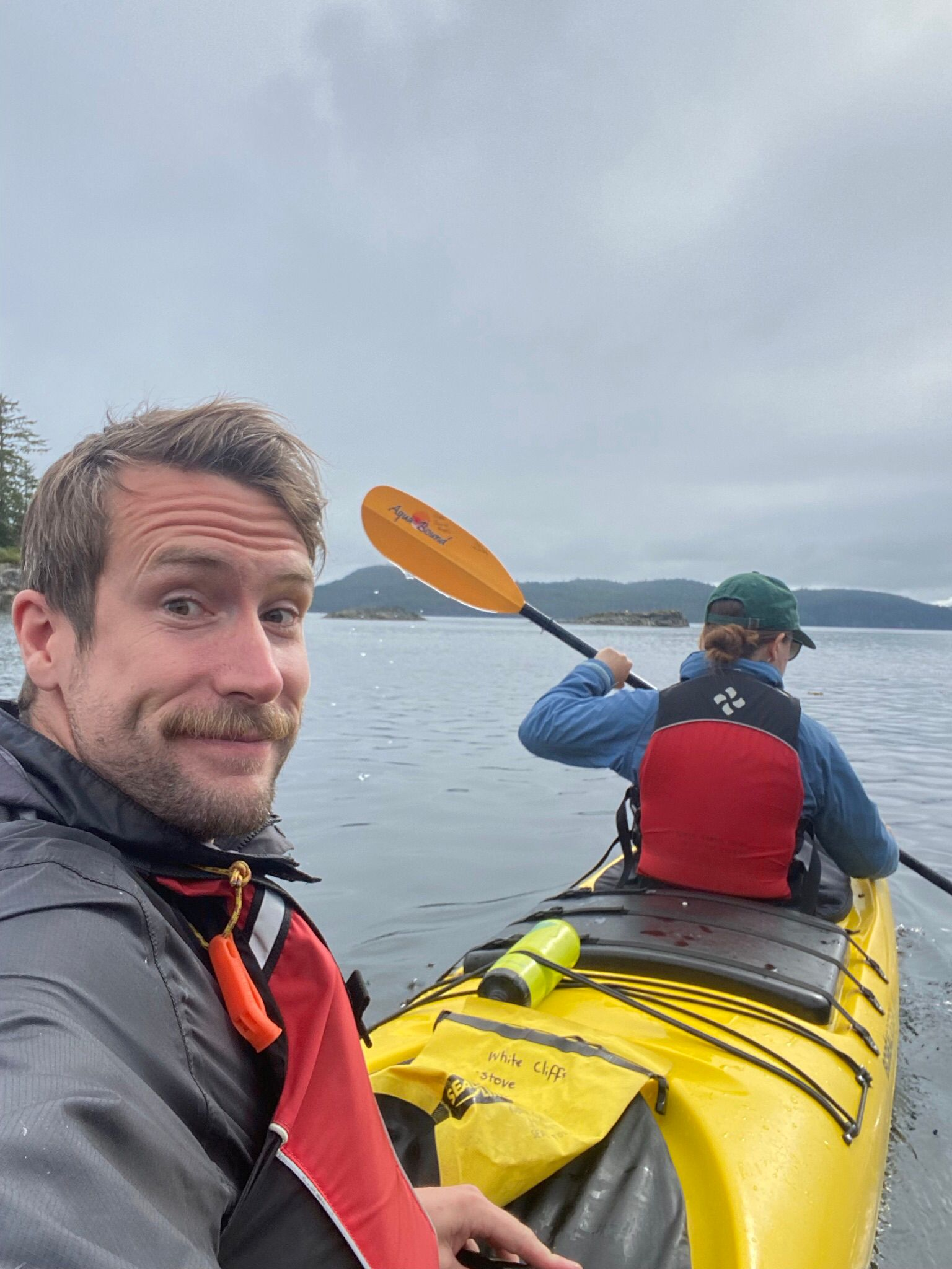 A man and woman kayaking in a yellow kayak under cloudy skies fundraising.